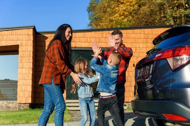 Eine glückliche familie steht zusammen in der nähe des autos und ihres hauses, bevor sie einen familienurlaub macht.
