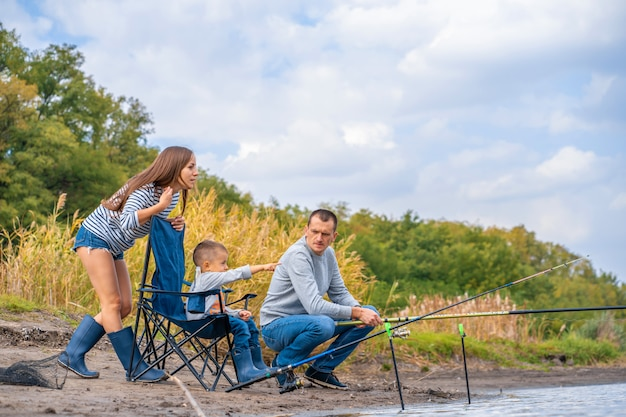 Eine glückliche familie verbringt zeit miteinander. sie bringen ihrem sohn das fischen bei.