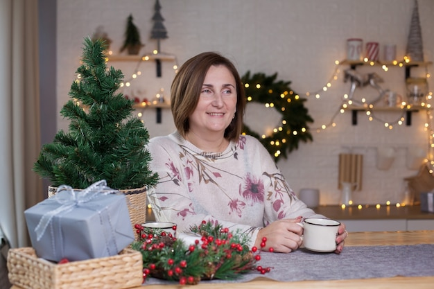 Eine glückliche frau, die an einem tisch sitzt und heiße schokolade im weihnachtlich dekorierten raum trinkt.