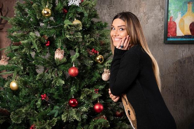 Eine glückliche frau im warmen pullover, der nahe weihnachtsbaum aufwirft. hochwertiges foto