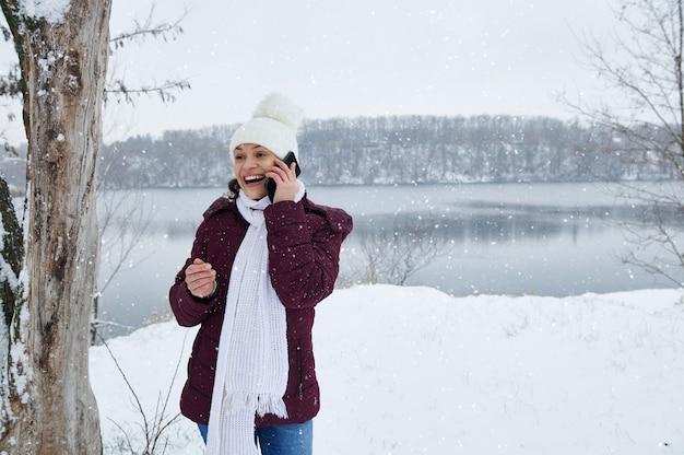 Eine glückliche frau in der warmen winterkleidung, die am telefon auf der schneebedeckten natur spricht, während schnee auf dem seehintergrund fällt