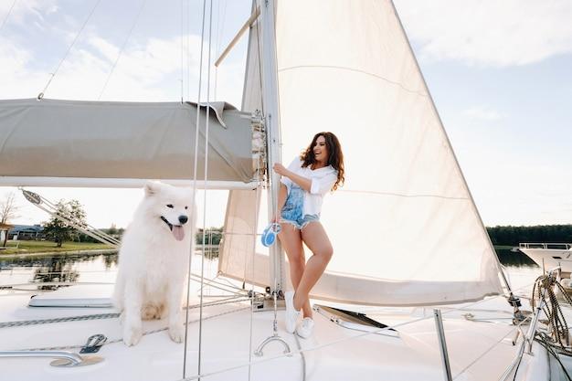 Eine glückliche frau mit einem großen weißen hund auf einer weißen yacht im meer