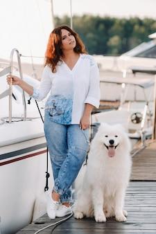 Eine glückliche frau mit einem großen weißen hund steht auf dem pier in der nähe der yacht.