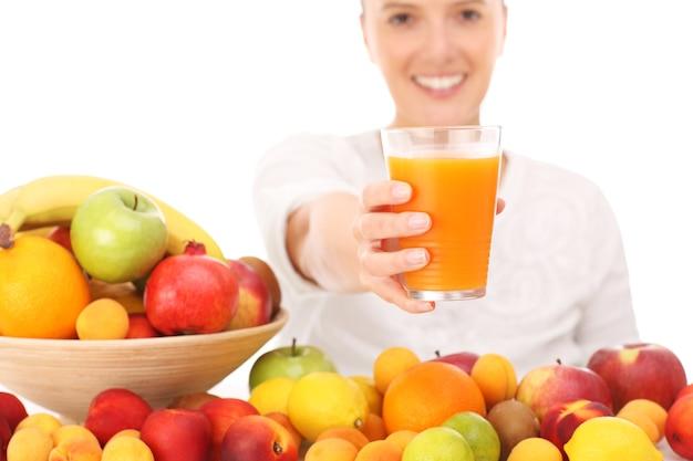 Eine glückliche frau mit fruchtsaft auf weißem hintergrund