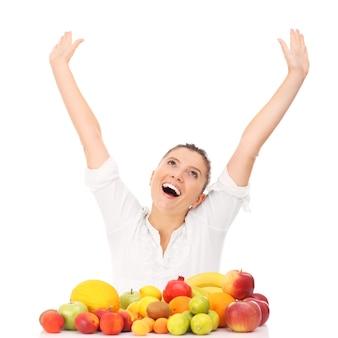 Eine glückliche frau mit früchten auf weißem hintergrund