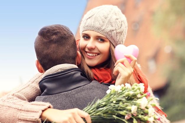 Eine glückliche frau mit valentinsgeschenk und blumen umarmt ihren mann