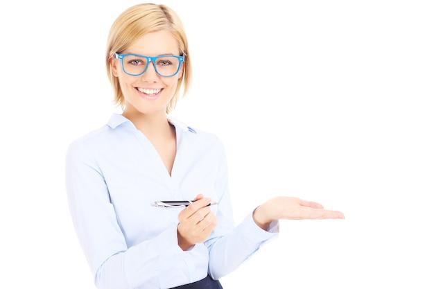 Eine glückliche geschäftsfrau mit einem stift, der etwas auf weißem hintergrund zeigt