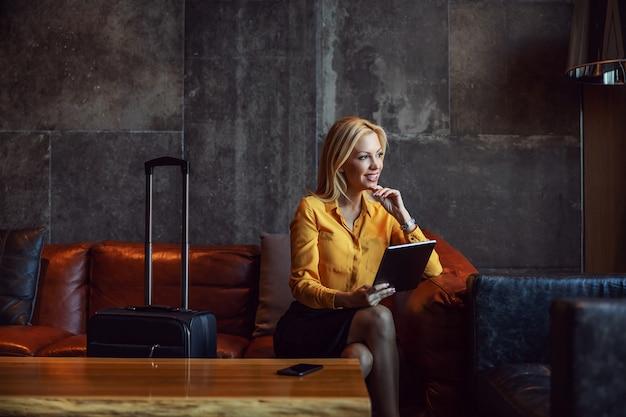 Eine glückliche geschäftsfrau sitzt in der hotellobby, checkt online im hotel ein und schaut nachdenklich aus dem fenster. er ist auf geschäftsreise. telekommunikation, reisen, geschäftsreisen