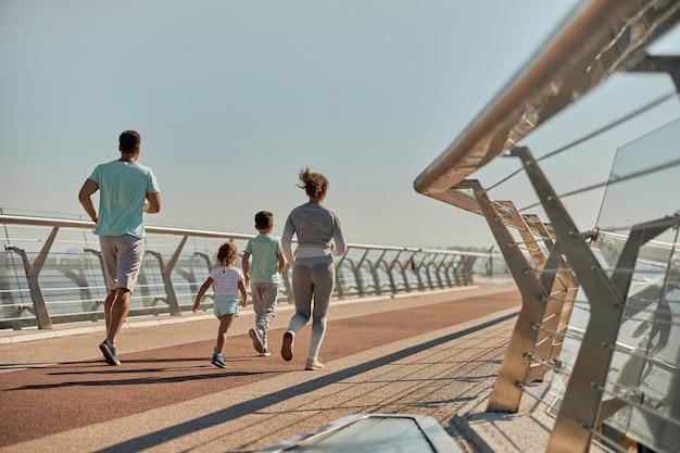 Eine glückliche, gesunde und sportliche familie trainiert an einem sonnigen tag