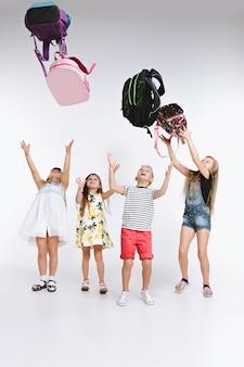 Eine glückliche gruppe von süßen und entzückenden teenagerkindern oder studenten ist wieder in der schule. über weißem studiohintergrund. das konzept freundschaft, bildung, kindheit, kindermode