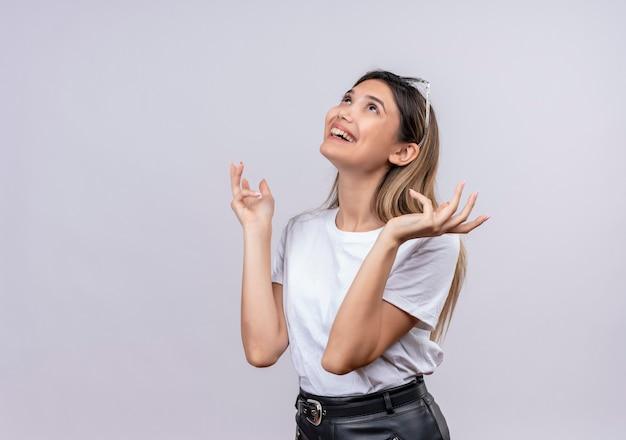 Eine glückliche hübsche junge frau im weißen t-shirt, das sonnenbrille auf ihrem kopf trägt, denkt und hebt glücklich ihre hände, während sie auf eine weiße wand schaut