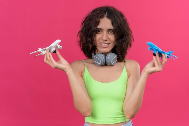 Eine glückliche junge attraktive frau mit kurzen haaren im grünen erntedach in kopfhörern, die weiße und blaue spielzeugflugzeuge halten
