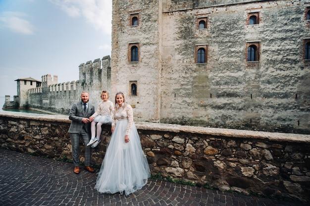 Eine glückliche junge familie geht durch die altstadt von sirmione in italien