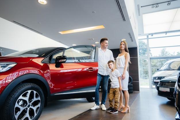 Eine glückliche junge familie wählt und kauft ein neues auto bei einem autohaus. ein neues auto kaufen.