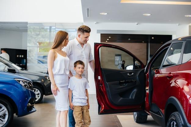 Eine glückliche junge familie wählt und kauft ein neues auto in einem autohaus. kauf eines neuen autos.