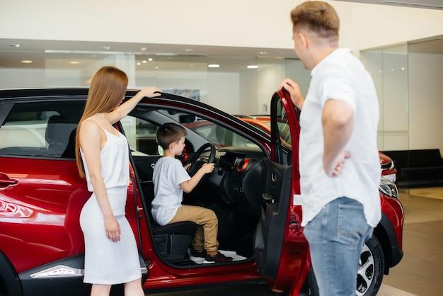Eine glückliche junge familie wählt und kauft ein neues auto in einem autohaus