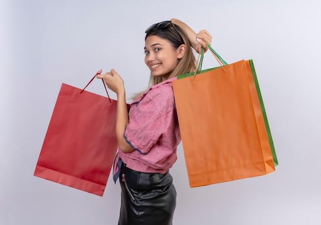 Eine glückliche junge frau, die rotes hemd trägt, das bunte einkaufstaschen zeigt, während auf einer weißen wand schaut