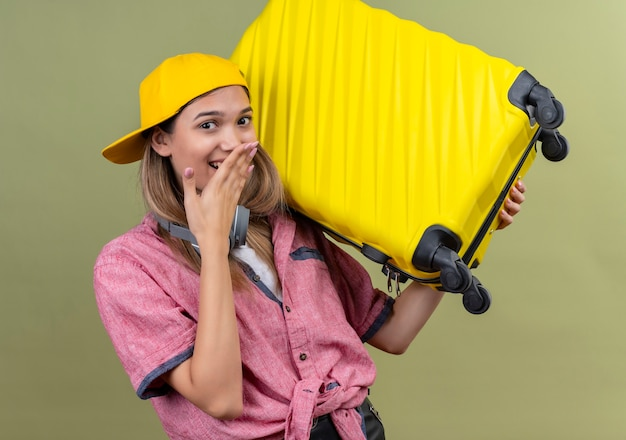 Eine glückliche junge frau, die rotes hemd und gelben baseballhut trägt, der mit hand auf mund lächelt, während gelben koffer auf einer grünen wand hält