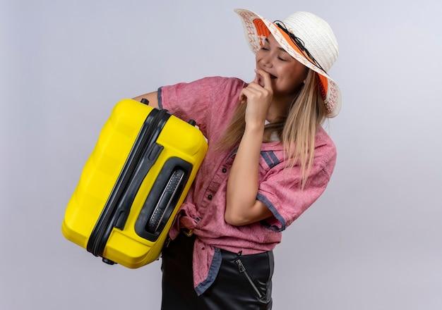 Eine glückliche junge frau, die rotes hemd und sonnenhut trägt, hält hand auf mund, während sie einen gelben koffer auf einer weißen wand trägt