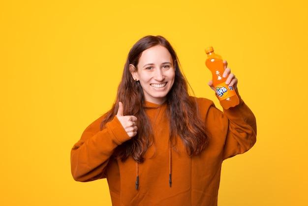 Eine glückliche junge frau hält eine fanta-flasche und zeigt einen lächelnden daumen