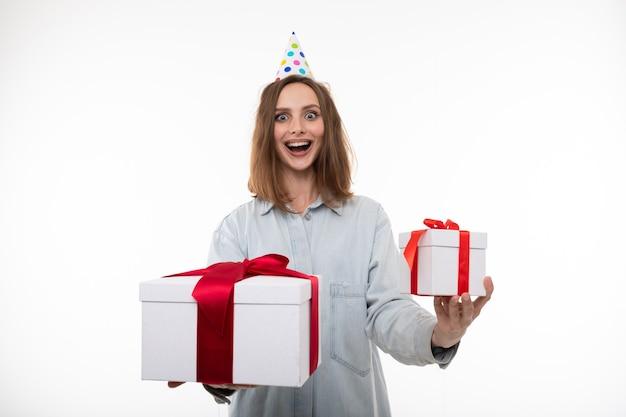 Eine glückliche junge frau in einem festlichen hut hält zwei geschenke auf einem weißen hintergrund