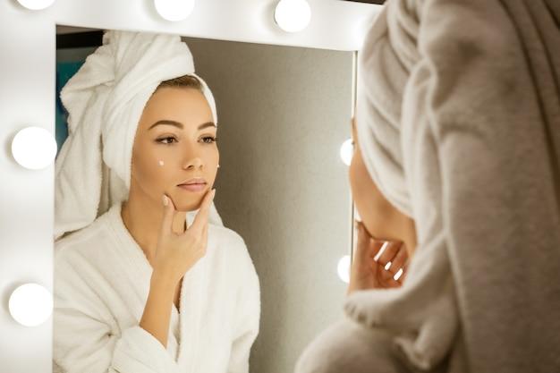 Eine glückliche junge frau in einem handtuch vor einem spiegel trägt creme auf ihr gesicht auf, ein konzept der hautpflege zu hause