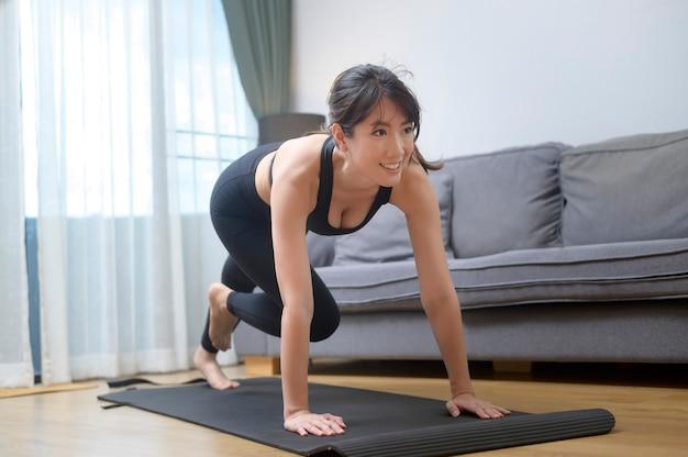 Eine glückliche junge frau in sportkleidung trainiert zu hause im wohnzimmer