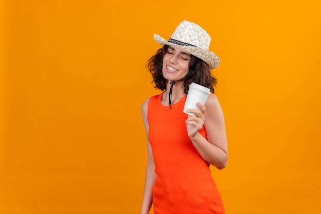 Eine glückliche junge frau mit kurzen haaren in einem orangefarbenen hemd, das sonnenhut hält, der plastikbecher kaffee hält