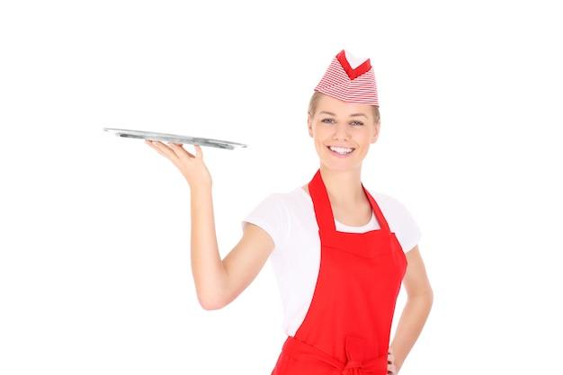 Eine glückliche kellnerin posiert mit einem serviertablett auf weißem hintergrund