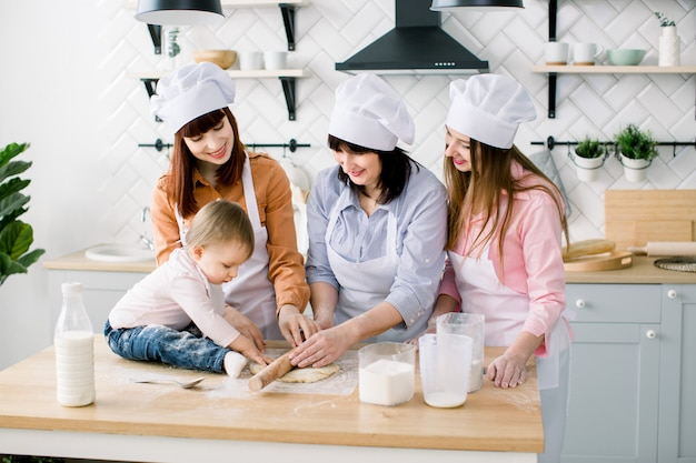 Eine glückliche, liebevolle familie bereitet gemeinsam eine bäckerei vor. großmutter, zwei töchter und enkelin backen kekse und haben spaß in der küche. hausgemachtes essen und kleiner helfer.