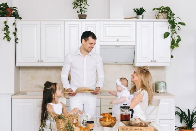 Eine glückliche, liebevolle familie bereitet gemeinsam eine bäckerei vor. mutter vater und zwei tochter mädchen kochen kekse und haben spaß in der küche. hausgemachtes essen und kleiner helfer.