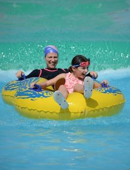 Eine glückliche moslemische familie der mutter und der tochter im swimmingpool