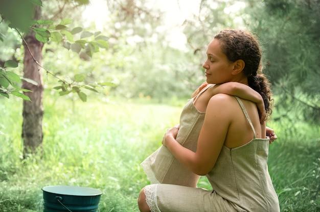 Eine glückliche mutter, die ihre tochter umarmt, auch in einem leinenkleid gekleidet. saison der kirschernte. schöne sonnenstrahlen fallen auf den obstgarten