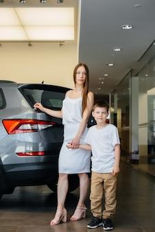 Eine glückliche mutter mit ihrem kleinen sohn wählt ein neues auto bei einem autohaus. ein auto kaufen.