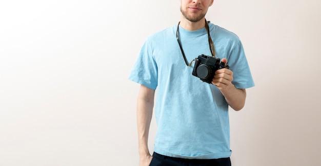 Eine glückliche person, die eine alte alte kamera hält und fotos macht