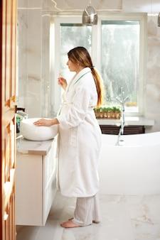 Eine glückliche schöne schwangere frau in einem bademantel putzt ihre zähne. lebensstil. schönes interieur. morgen- und abendroutine. gesundheitsvorsorge. zahnpflege. foto in hoher qualität