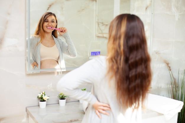 Eine glückliche schöne schwangere frau in einem bademantel putzt ihre zähne. spiegelung im spiegel. schönes interieur. morgen- und abendroutine. gesundheitsvorsorge. zahnpflege. foto in hoher qualität