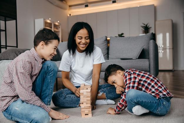 Eine glückliche schwarze familienmutter und zwei söhne, die eine runde jenga spielen