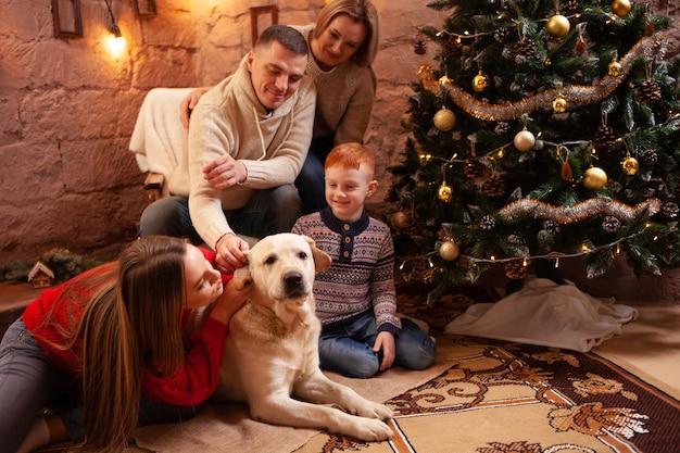 Eine glückliche vierköpfige familie und ein hund feiern das neue jahr