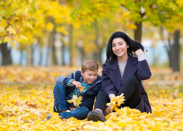 Eine glückliche, zufriedene mutter und ein sohn, die in einem stadtpark zwischen gelbem herbstlaub sitzen und spielen.