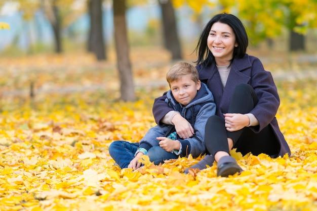 Eine glückliche, zufriedene mutter und ein sohn, die in einem stadtpark zwischen gelbem herbstlaub sitzen.