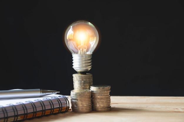 Eine glühlampe auf stapel münzen für geschäfts- und buchhaltungskonzept.