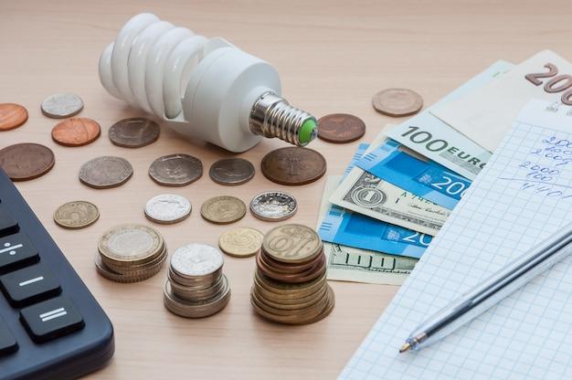 Eine glühlampe, ein notizbuch mit einem stift, rechnungen, verschiedenes geld und ein taschenrechner auf dem tisch.