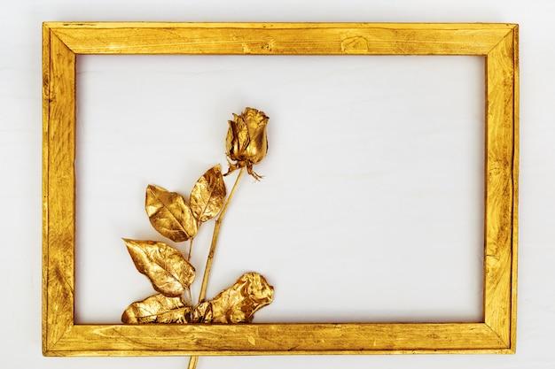 Eine golden bemalte rose im holzrahmen