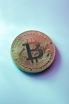 Eine goldene bitcoin isoliert auf blauem hintergrund nahaufnahme mit kopierraum