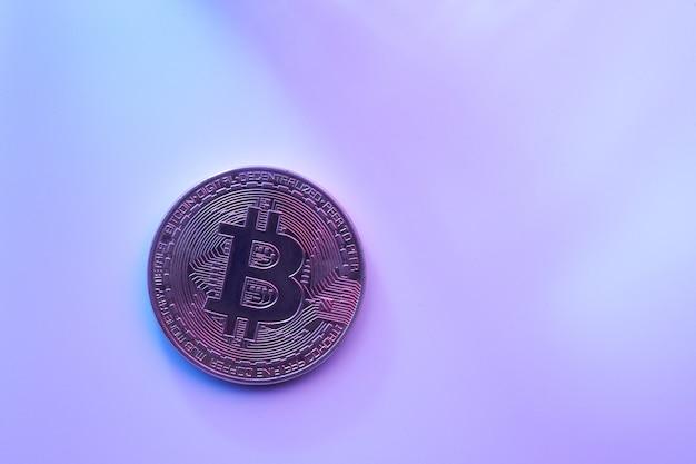 Eine goldene bitcoin isoliert auf rosa lila hintergrund nahaufnahme mit kopierraum