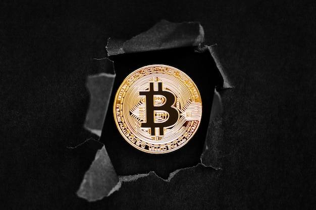 Eine goldene bitcoin-zeichensymbolikone, die durch den hintergrund platzt