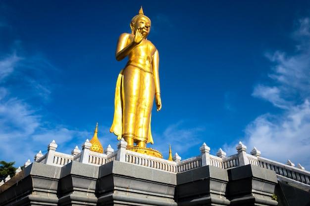 Eine goldene buddha-statue auf dem altar für die anbetung auf einem schönen hintergrund des blauen himmels.