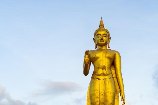 Eine goldene buddha-statue mit himmel auf der bergspitze im öffentlichen park der gemeinde hat yai, provinz songkhla, thailand