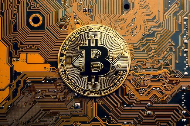 Eine goldene münze mit bitcoin-symbol auf einem mainboard.